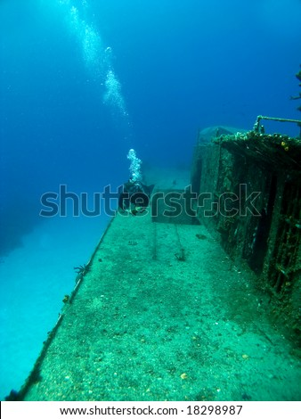 Diver swimming along side a Sunken Shipwreck in Cayman Brac