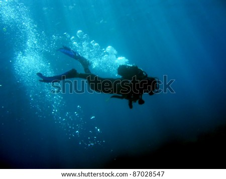 Diver with bubbles and sun rays against black bottom