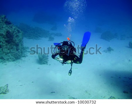 Diver with camera in deep and bubbles. Underwater photographer