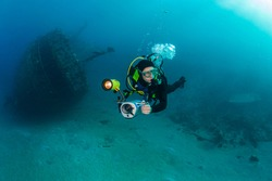 Diver with underwater video camera dives near the wreck, Red Sea.