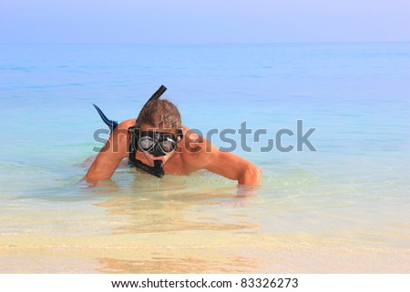 Diver withTube and mask for a scuba diving on seacoast with sand