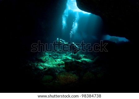 Divers exploring a Lava Tube in South Kona Hawaii
