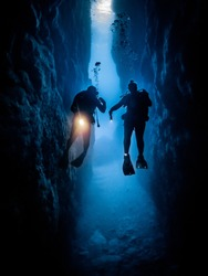 divers exploring through a tunnel