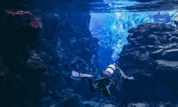 Divers scuba diving between two tectonic plates in crystal clear glacier water blue transparent underwater Silfra Iceland view Great visibility volcanic lava rocks stones formations, air tank dry suit