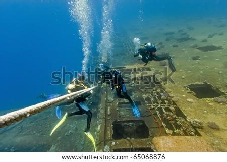 Divers under wreck
