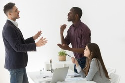 Diverse african and caucasian colleagues disputing at group meeting, multiracial partners having conflict disagreement during negotiations, three multi-ethnic coworkers team arguing at workplace