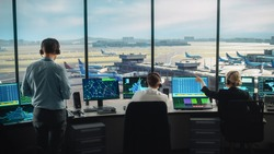 Diverse Air Traffic Control Team Working in a Modern Airport Tower. Office Room is Full of Desktop Computer Displays with Navigation Screens, Airplane Flight Radar Data for Controllers.
