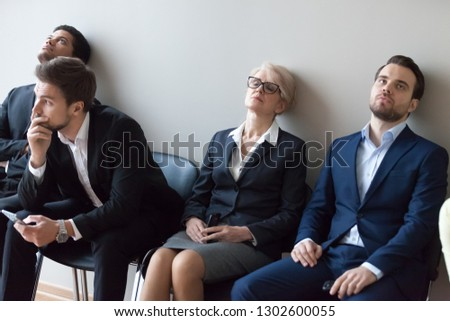 Diverse applicants getting bored sitting on chairs in queue line tedious waiting for job interview concept, tired exhausted multi-ethnic seekers candidates fatigued annoyed with delay or long await