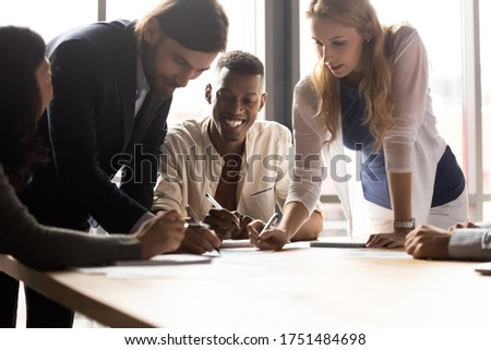 Diverse associates gathered in boardroom leaned over desk writing project plan and ideas do paperwork at group meeting briefing, analyzing market, having fun, teamwork, fun team building games concept ストックフォト ©
