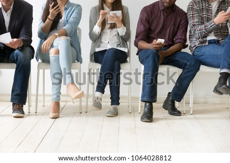 Diverse black and white people sitting in row using smartphones tablets, multiracial men and women waiting for job interview, human resources, employment or customers and electronic devices concept stock photo