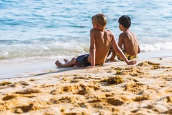 diverse boys are playing, sitting together at the beach and watching sea waves. diversity children friendship.