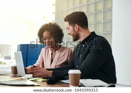 Diverse business colleagues sitting at a desk in a modern office talking together over a laptop