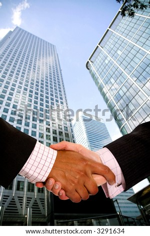 diverse business men shaking hands in a corporate environment - vertical