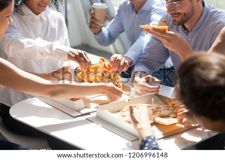 Diverse business office people group taking sharing pizza slices from box on table, staff employees team workers eating together enjoy lunch at work break, delivery service concept, close up view