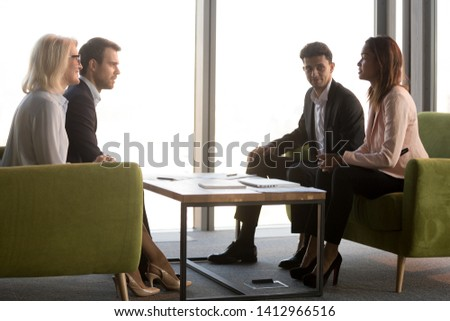 Diverse business partners sit in office having conversation discussing potential cooperation, businesspeople negotiate in conference room, brainstorming talking at briefing. Partnership concept