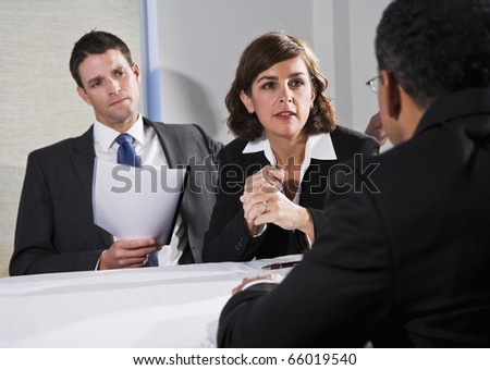 Diverse business people conversing and negotiating, focus on businesswoman, 40s