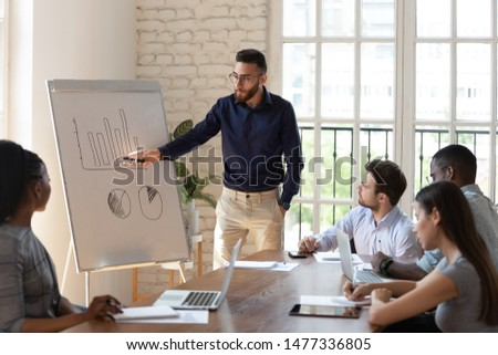 Diverse business people group listen to male speaker presenter coach giving flip chart presentation at lecture training workshop meeting in office explain corporate growth strategy in conference room
