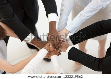 Diverse business people group put hands together in stack pile at training as concept of sales team corporate unity connection, teambuilding loyalty, support in teamwork, coaching, close up top view