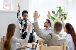 Diverse business people group raise hands at corporate presentation training, happy multi-ethnic employees team participate in vote volunteering, ask questions at conference with african coach leader