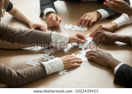 Diverse business people helping in assembling puzzle, cooperation in decision making, team support in solving problems and corporate group teamwork concept, close up view of hands connecting pieces