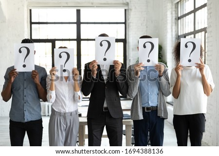 Diverse business people hiding faces behind papers sheets with question marks, standing in row in office. Identity and equality employee at work, candidates waiting for job interview, recruitment.