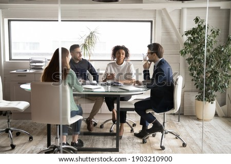 Diverse business people partners discussing project, contract terms, brainstorming in modern board room behind glass wall, colleagues sitting at table in office, talking, sharing startup ideas Photo stock ©
