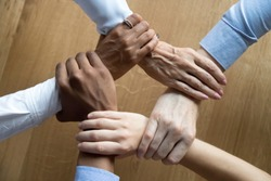 Diverse business people team connected grasping hands holding each other wrists in circle, loyalty help in teamwork concept, professional trust power support unity solidarity, close up top view above