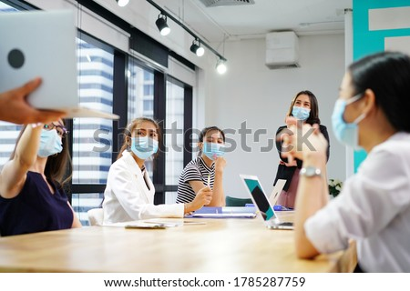 diverse business worker discuss and meeting while Wearing Medical Mask as protection from corona virus. New normal office working. Group of multiethnic people in business reopen. flu prevent healthy