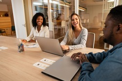diverse business workgroup in informal conversation in meeting room