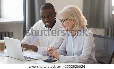 Diverse businessman and businesswoman accountants working together on pc discussing online software business strategies collaborating on computer, office colleagues team planning project use laptop