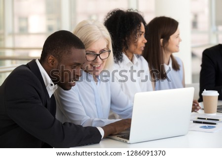 Diverse businessmen and businesswoman sitting together with laptop in boardroom during business meeting negotiations, focus on middle-aged company owner and black employee looking at computer screen