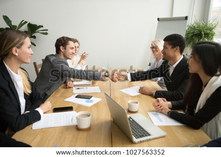 Diverse businessmen shaking hands after signing contracts at group multiracial meeting, african and caucasian partners in suits handshaking promising good deal after successful negotiations concept