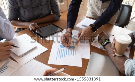 Diverse businesspeople discuss financial report in charts diagrams and graphs close up above view, business partners analysing common sales statistics presenting deal benefits at group meeting concept