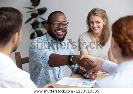 Diverse businesspeople during seminar, black business trainer greeting female company executive manager gathered together with staff employees for improve knowledge be successful in business sphere