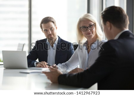 Diverse businesspeople negotiate at office meeting discussing startup project with clients, company managers have conversation with business partner, consider collaboration. Partnership concept