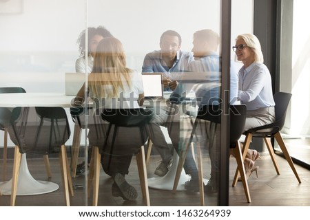 Diverse businesspeople sit at office desk brainstorm together discuss project at meeting, multiethnic employees talk negotiate in conference room share ideas cooperating in boardroom at briefing