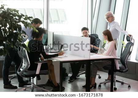 Diverse businesspeople sit in coworking space busy working discussing ideas together, multiracial concentrated colleagues coworkers engaged in office daily life activity in shared workplace
