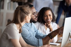 Diverse businesspeople working in shared office, focus on black american team leader sitting at desk together with females colleagues, mentor helps understand research data company corporate program