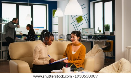 Diverse businesswomen discussing new project for company evolution, black woman checking tasks on clipboard, signing new contract. Multiethnic employees gathered in co-working space Photo stock ©
