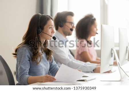 Diverse call center workers sitting in row, focus on customer service member girl in headset looks at pc screen hold paper talk with potential client provide insurance information sell company product