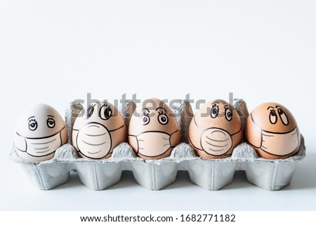Diverse chicken eggs with doodle faces wearing medical masks with white background. Conceptual image of pollution and epidemy