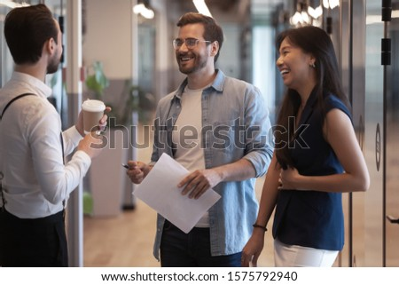 Diverse colleagues met in modern office hallway having informal positive conversation, asian girl laughing enjoy break at workday with european guys multi racial friendship good work relations concept