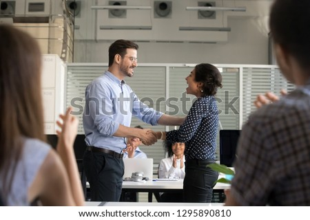 Diverse colleagues shaking hands standing in office. Company owner congratulate indian employee with reward or promotion. Millennial hindu female leader worker feels happy getting advancement at work