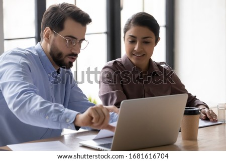 Diverse colleagues sit at office desk work on laptop discuss business project together, concentrated multiracial coworkers cooperating using computer brainstorm at meeting in boardroom