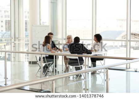 Diverse colleagues sit at table, discussing project at company meeting in board room, employees team talking about business strategy, marketing plan at briefing, negotiations with business partners