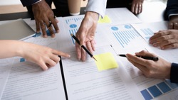 Diverse corporate staff discuss report shown in charts and graphs, analyzing financial stats, involved in project overview, reviewing results, close up. Employees participate in brainstorming concept