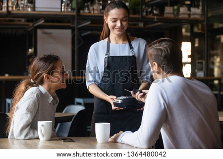 Diverse couple buyers male female pub bar client pay bill order use cellphone smartphone app near field communication system. Modern fast easy tech NFC contactless payment, food drink industry concept #1364480042