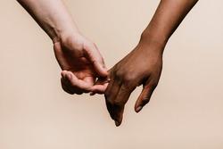 Diverse couple holding hands closeup