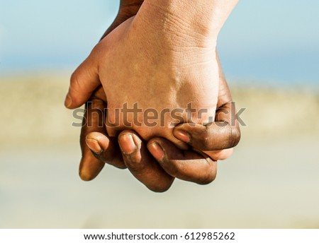 Diverse culture and race couple hands in love romantic moments outdoor - Black man and white woman in tender situation against racism - Soft focus on bottom finger - Warm filter