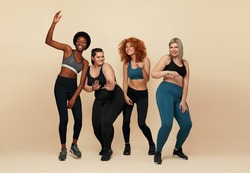 Diverse. Different Women Dancing Portrait. Diversity Figure And Size Models Full-Length Portrait. Group Of Multicultural Friends In Sportswear Posing On Beige Background. Body Positive As Lifestyle.
